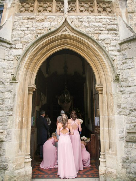 Back view of Bridesmaids arriving at Abbey a framed by arch at Fulham Palace London