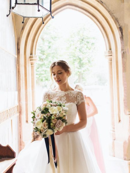 Bride holding relaxed bouquet of flowers with blue ribbons about to walk down aisle at Abbey a framed by arch at Fulham Palace London