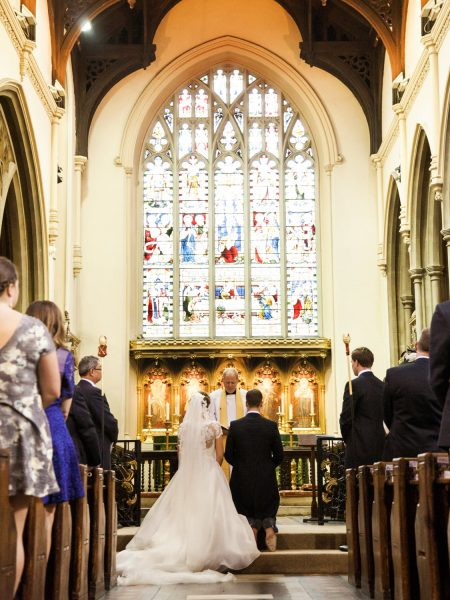 Bride and Groom kneeing at front of church with large stained window in background at the Abbey Fulham Palace London