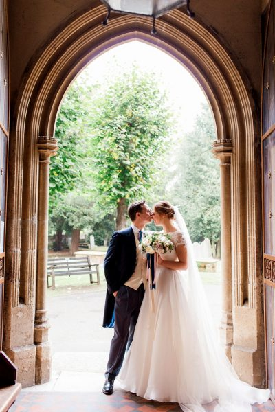 Bride and Groom kiss post ceremony under arch of Abbey at Fulham Palace London