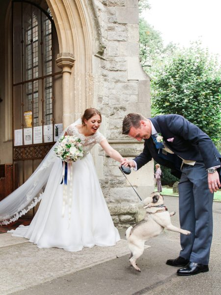 Bride and Groom with bouncy pug dog outside the Abbey at Fulham Palace London