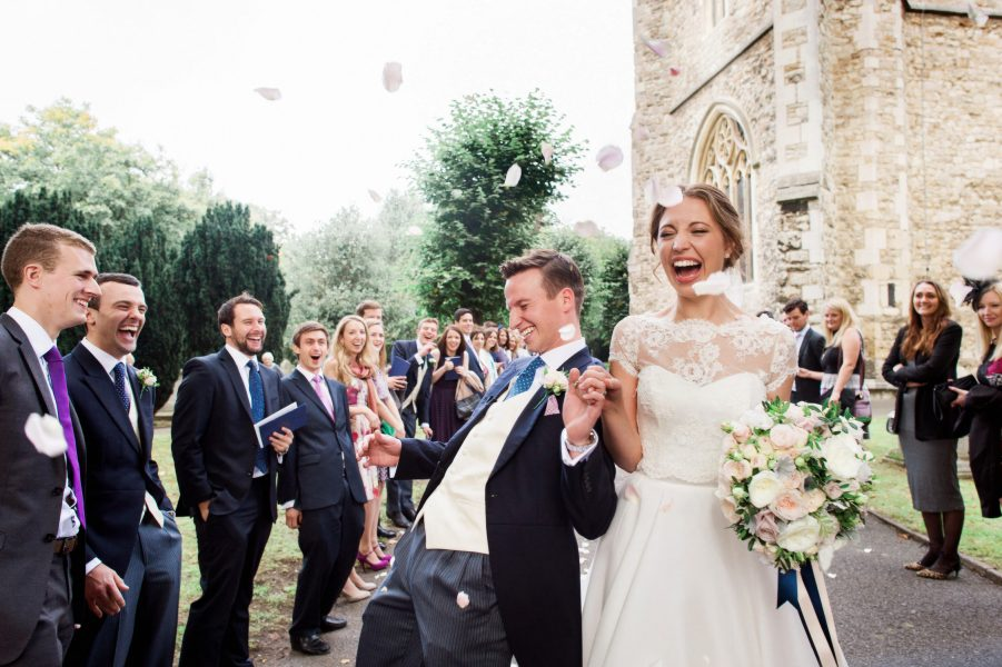 Bride and Groom laugh as they enjoy confetti being thrown by wedding guests outside the Abbey at Fulham Palace London