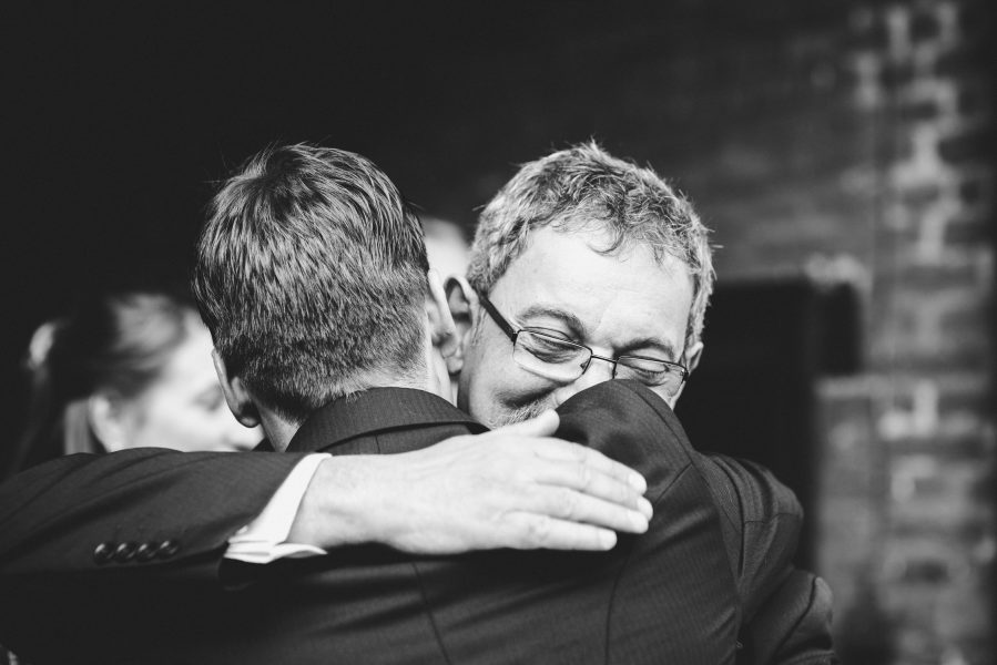 Father of the Bride hugs Groom post ceremony
