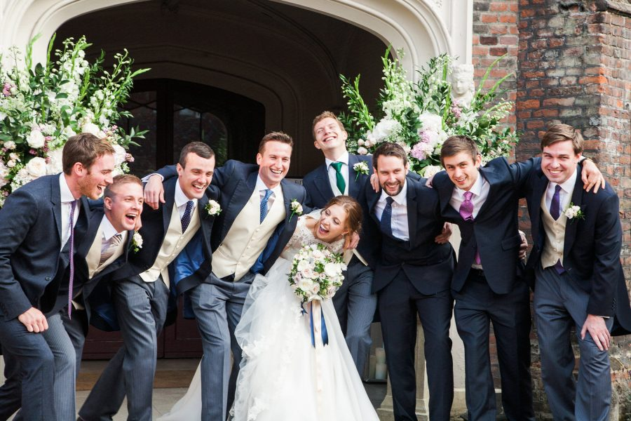 Bride laughing with Groom and ushers during portraits at Fulham Palace London