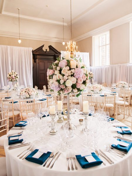Wedding breakfast room decorated with soft pink florals and blue napkins at Fulham Palace London
