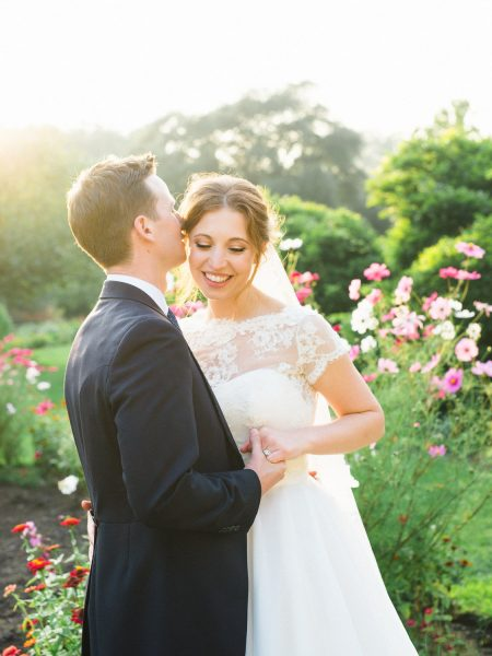 Fine art portrait of Groom kissing Bride in the gardens of Fulham Palace London