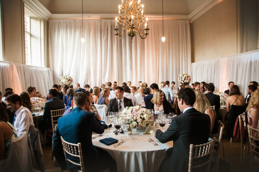 Wide shot of wedding breakfast room with guests chatting at Fulham Palace London