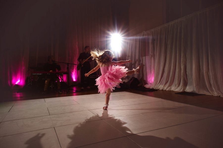 Young girl in pink tutu dancing a high kick on wedding dance floor at Fulham Palace London