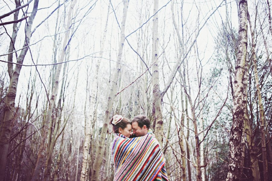 Winter Engagement LOVE shoot with couple snuggling under multicoloured stripy blanket with a backdrop of silver birch forest