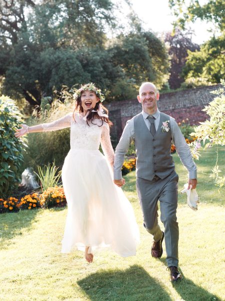 Fine Art Bride and Groom Portrait with Bride in Jay Archer floral crown and Groom in grey suit jumping for joy at Fulham Palace London