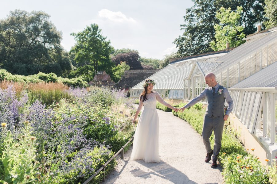 Fine Art Bride and Groom Portrait with Bride twirling as Groomplayfully walk holding hands arms extended while looking at each other Fulham Palace London herb gaden and flower bed