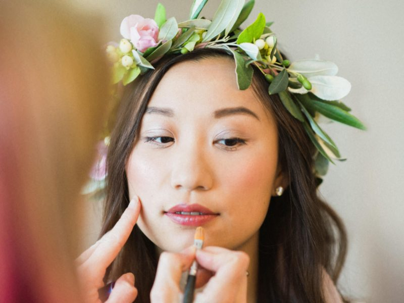 Fine Art Portrait of the Bride in a pastel floral crown having her lips painted for a London wedding
