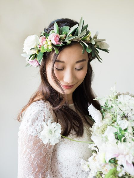 Fine Art Portrait of the Bride wearing Anna Kara in floral crown holding bouquet of rustic country flowers looking down in a pastel floral crown having her lips painted for a London wedding