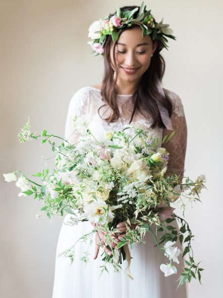 Fine Art Portrait of the Bride looking down at her loose floral bouquet of wild roses with trailing foliage in a long sleeved Anna Kara dress in floral crown holding bouquet of rustic country flowers looking down in a pastel floral crown having her London wedding