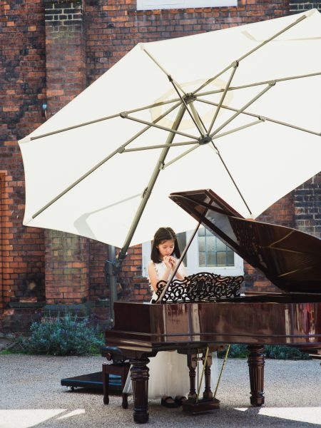 Young piano player girl standing behind grand piano during outdoor wedding ceremony Fulham Palace London