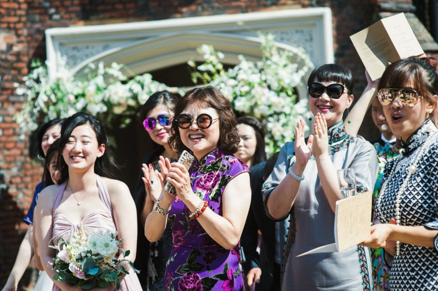 Chinese guests clap congratulations to the Bride and Groom during at wedding ceremony Fulham Palace London wedding