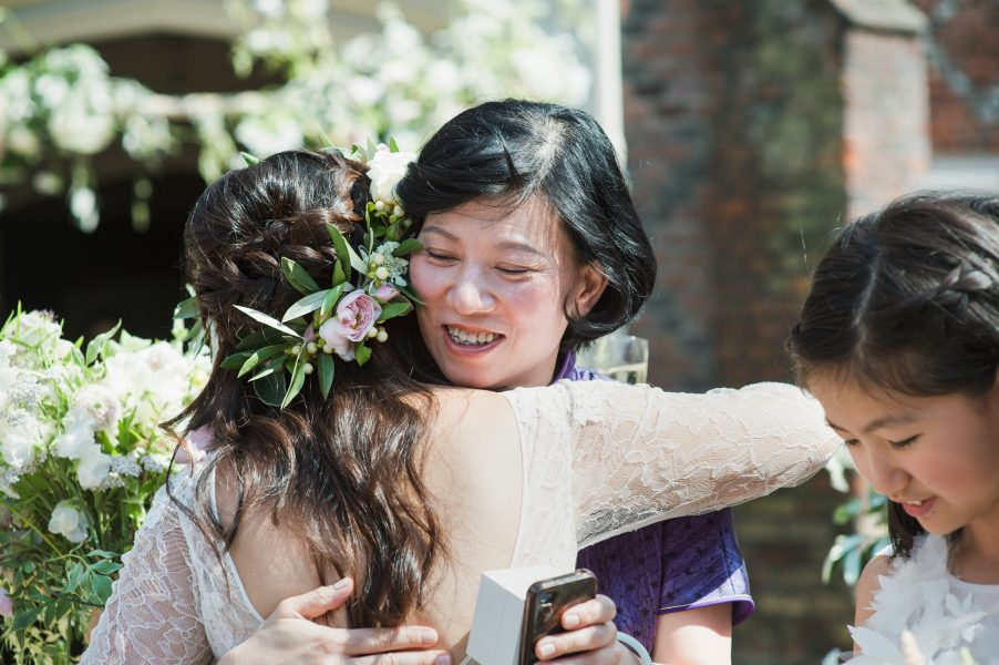 Mother of Bride hugging Bride in an emotional embrace after the outdoor wedding ceremony Fulham Palace London wedding