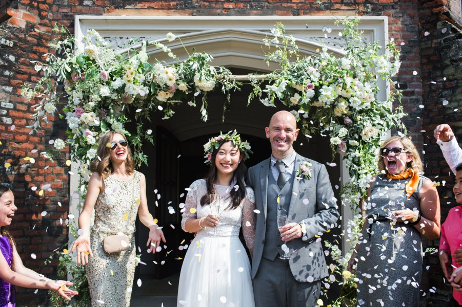Guests throw confetti over the Bride and Groom as they stand under the arch architecture of Fulham Palace London