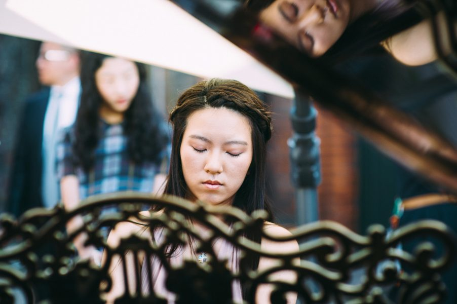 Chinese wedding Guest head shot as she plays piano and her reflection in the wood as she plays the grand piano through decorative wood piano detail Fulham Palace London wedding