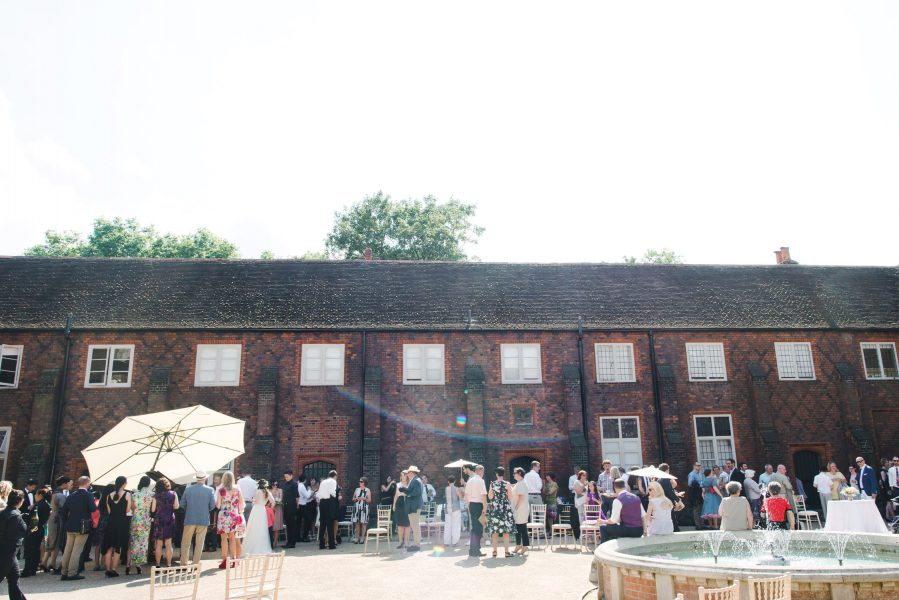 Guests enjoying the cocktail hour drinks reception in the courtyard at Fulham Palace London behind the spray of the fountain