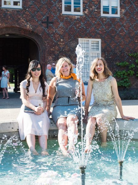 Guests sitting on edge of fountain cooling feet off in the courtyard at Fulham Palace London behind the spray of the fountain at Fulham Palace London