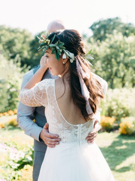 Fine art wedding portrait of Bride with back to camera in a Anna Kara dress and floral crown and Groom with hands around Bride's waist in the gardens of Fulham Palace