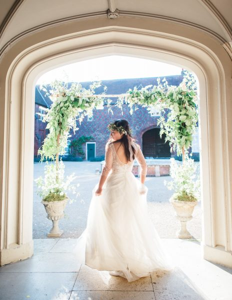 Fine Art portrait of Bride in Jay Archer floral crown joyfully spinning around under an architectural arch and floral arch at Fulham Palace London