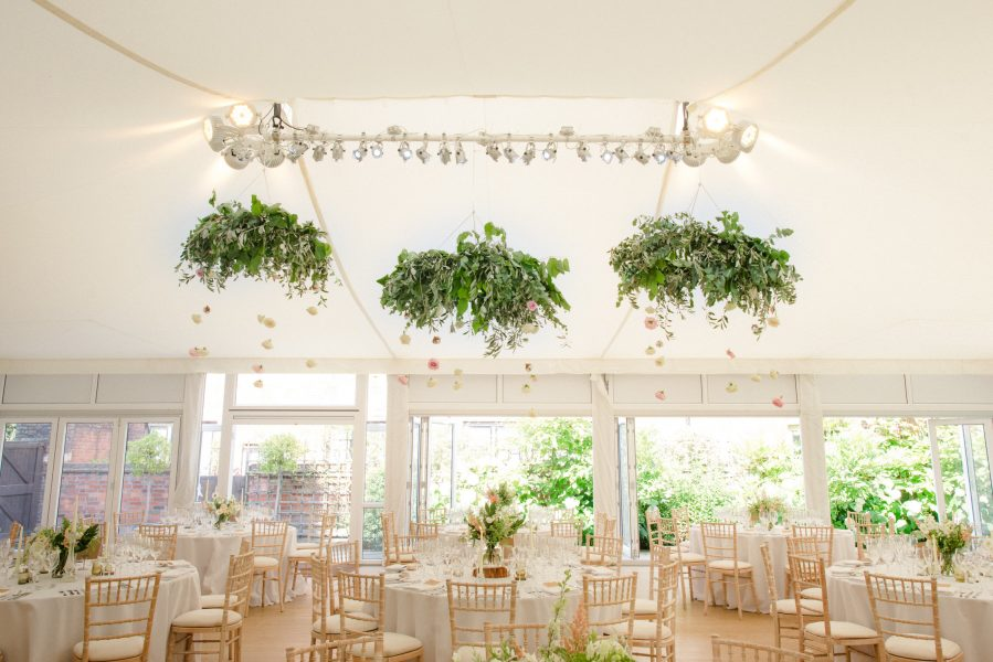 Marquee wedding decor of whole marquee including centre piece of natural relaxed country flowers in creams and dusky pastels there large suspended from ceiling of marquee rings of foliage at Fulham Palace London