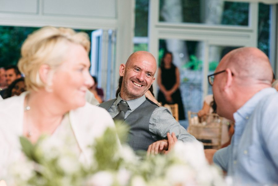 Groom laughing and exchanging conversation with happy wedding guest during reception Fulham Palace London