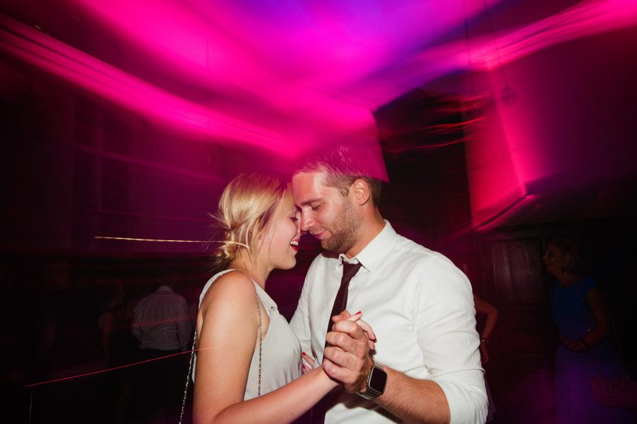 Wedding guest couple dance emotionally together on the dance floor with pink light trails