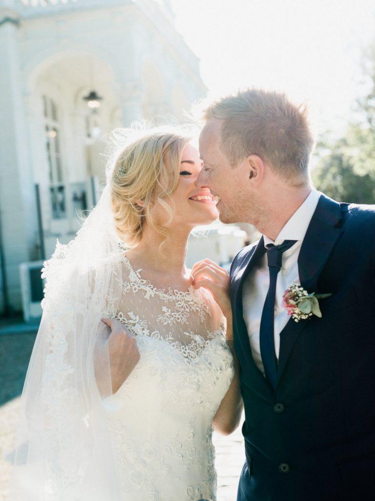 Fine Art portrait of Bride and Groom kissing. Kokkedal Slot Copenhagen in the background