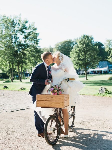Fine Art portrait of Bride and Groom kissing. A Velorbis bike stands in-between them with Kokkedal Slot Copenhagen grounds in the background