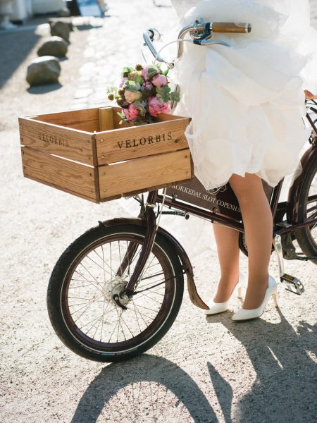 Fine Art portrait of Bride on a Velorbis bike with peony bouquet decorating bike at Kokkedal Slot Copenhagen