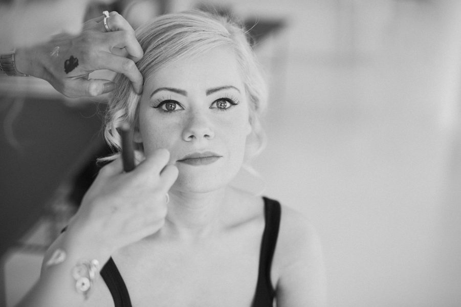 Black and white portrait of Bride having her make up applied