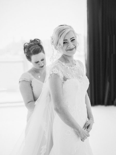 Black and white portrait of Bridesmaid buttoning up back of Bride's dress