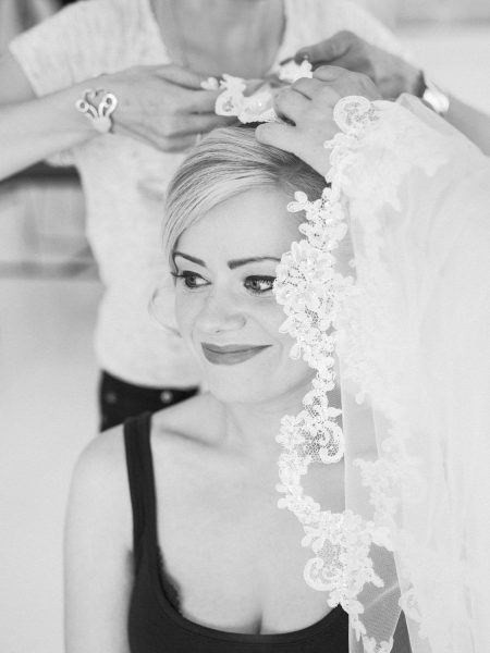 Black and white portrait of Bride having her veil styled into her hair