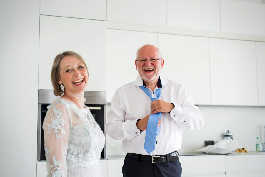 Father of the bride doing blue tie up laughing with Mother of the Bride