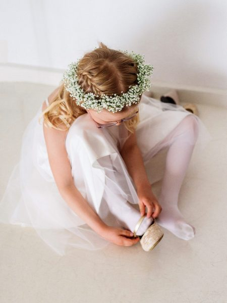 Sweet flower girl wearing gypsophila floral crown putting pretty shoes on