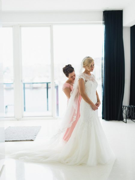 Full length image of Bridesmaid buttoning up Bride's dress