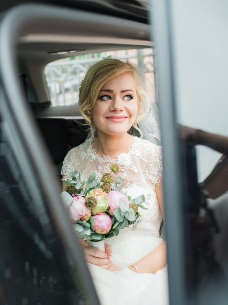 Bride with tears in eyes about to step out of wedding car