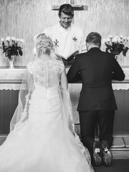 Back view of Bride and Groom kneeling at Sjømannskirken Kong Haakons Kirke