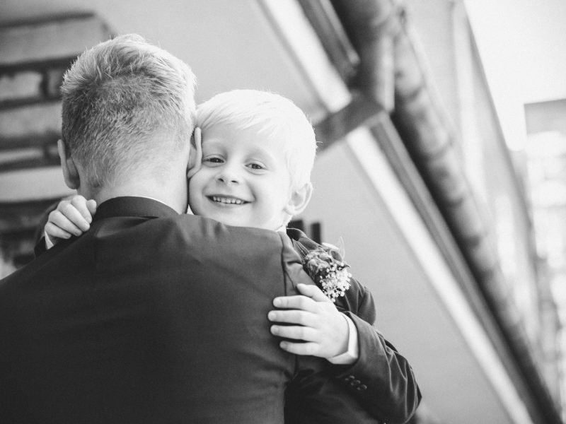 Page boy smiling as he hugs Groom outside Bride and Groom exchange rings at Sjømannskirken Kong Haakons Kirke