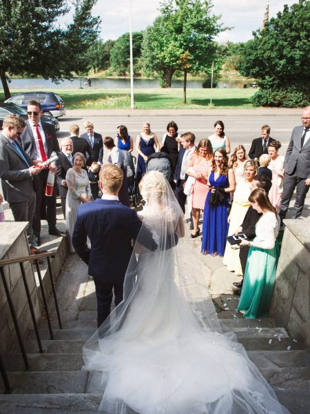 Full length back view of Bride and Groom looking down on wedding guests with lake in Copenhagen background