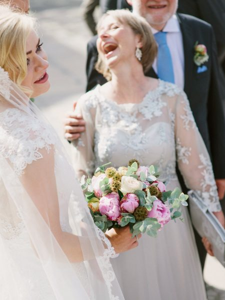 Mother of Bride laughing while Bride holds her pink peony and eucalyptus bouquet Sjømannskirken Kong Haakons Kirke