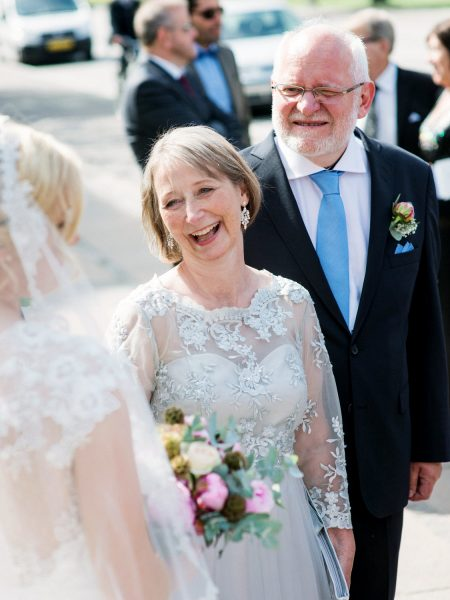 Mother of Bride smiling while Bride holds her pink peony and eucalyptus bouquet Sjømannskirken Kong Haakons Kirke