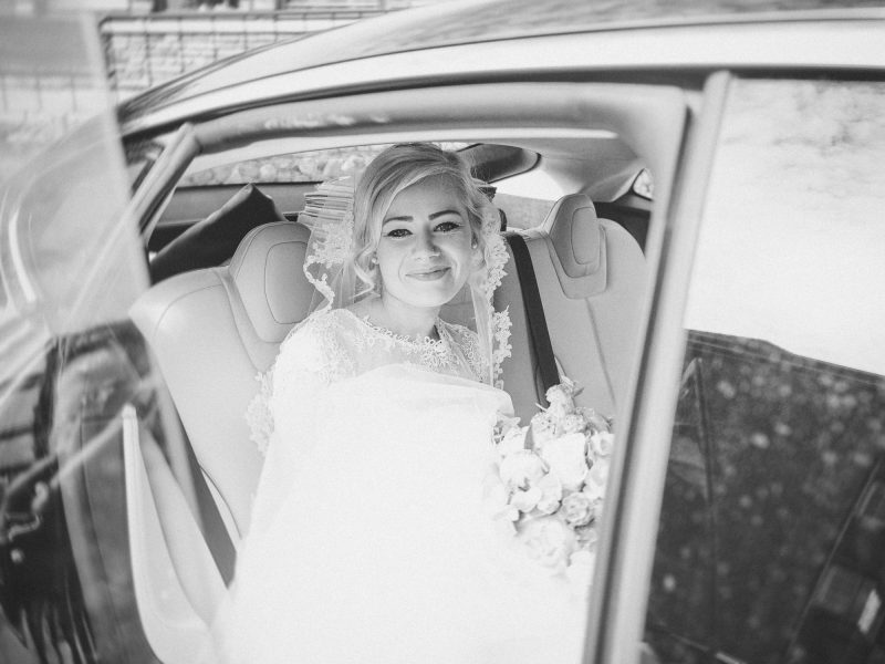 Bride smiling at camera after stepping into wedding car outside Church of Our Saviour, Copenhagen