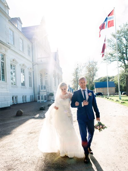Bride and Groom walking towards camera with Norwegian flag and Kokkedal Slot in background