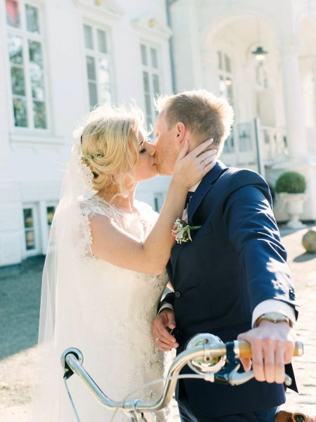 Fine Art portrait ofBride and Groom kissing in front of Kokkedal Slot in background