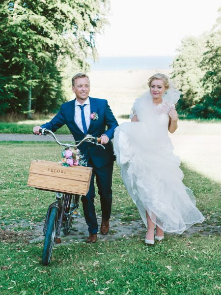 Bride and Groom walking away from Danish sea pushing a Velorbis bike at Kokkedal Slot Copenhagen