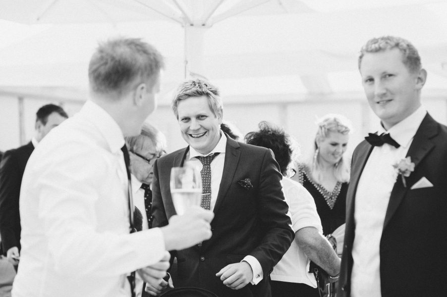 Wedding guests laughing during cocktail hour Kokkedal Slot Copenhagen